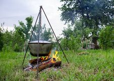 Un man' la mano de s enciende un fuego debajo de una cacerola, que se coloca en un fuego foto de archivo libre de regalías