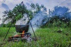 Un man' la mano de s enciende un fuego debajo de una cacerola, que se coloca en un fuego imagen de archivo