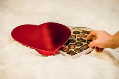 Un man& x27; mano di s che raggiunge per una scatola di cioccolato Immagine Stock