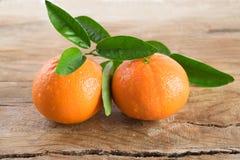Un mandarino due (mandarini) su fondo di legno Fotografia Stock Libera da Diritti