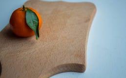 Un mandarino maturo con una foglia verde su una piattaforma di legno immagini stock libere da diritti