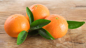 Un mandarino tre (mandarini) su fondo di legno Fotografia Stock