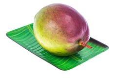 Un mango maduro en la placa foto de archivo
