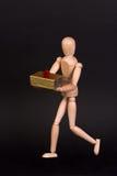 Un maniquí de madera con el presente Fotografía de archivo libre de regalías