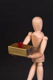 Un maniquí de madera con el presente Fotos de archivo libres de regalías