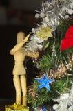 Un maniquí de madera que monta un árbol de navidad fotos de archivo libres de regalías