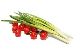 Un manojo de cebollas verdes y de tomates Imágenes de archivo libres de regalías