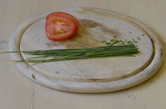 Un manojo de cebolletas y de rebanadas frescas de tomate en la tajadera de madera Imagenes de archivo