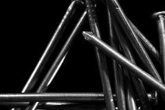 Un manojo de clavos en un fondo negro es macro, foco suave Imagen de archivo