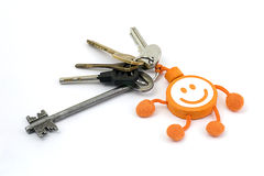 Un manojo de llaves con un llavero una cara sonriente en el fondo blanco Fotos de archivo libres de regalías