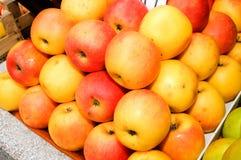 Un manojo de manzanas amarillas y verdes en la tabla en el mercado Foto de archivo