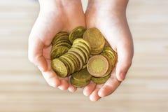 Un manojo de pequeñas monedas en las manos de un niño pequeño Imagen de archivo libre de regalías