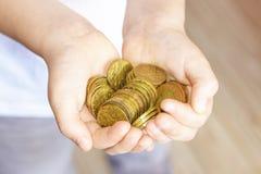 Un manojo de pequeñas monedas en las manos de un niño pequeño Fotografía de archivo libre de regalías