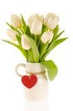 Un manojo de tulipanes blancos en un jarro con el corazón rojo Imagenes de archivo
