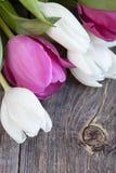 Un manojo de tulipanes frescos florece en un fondo de madera rústico Imagen de archivo libre de regalías