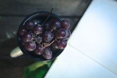Un manojo de uvas en una taza blanca Foto de archivo libre de regalías