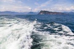 Un mar azul profundo con la isla en distancia con la ondulaci?n media de la onda de agua imagenes de archivo
