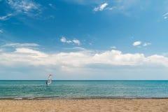Un mar reservado, cielo azul, persona que practica surf en el horizonte, playa Imágenes de archivo libres de regalías