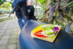 Un marché avec une boîte faite de feuilles, à l'intérieur d'une disposition des fleurs sur un motorcyle, dans la ville de Denpasa Photo libre de droits