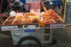 Un marchand ambulant vendant les insectes frits aux touristes sur la route de Khao San à Bangkok Image stock
