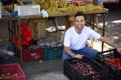 Un marchand de légumes vendant les fruits organiques. Photos stock