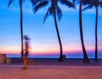 Un marcheur de début de la matinée est brouillé pendant qu'il passe entre deux palmiers silhouettés créés par le lever de soleil  Image libre de droits