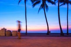 Un marcheur de début de la matinée est brouillé pendant qu'il passe entre deux palmiers silhouettés créés par le lever de soleil  Photos stock