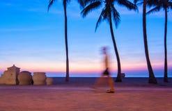 Un marcheur de début de la matinée est brouillé pendant qu'il passe entre deux palmiers silhouettés créés par le lever de soleil  Photographie stock