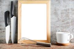 Un marco de madera vacío y accesorios de la cocina en un backgr de madera Fotos de archivo