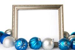 Un marco de plata vacío con los ornamentos de la Navidad del azul y de la plata Foto de archivo