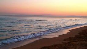 Un mare calmo di sera ondeggia in una baia con una spiaggia sabbiosa su un fondo del tramonto stock footage