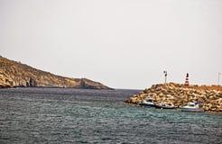 Un mare del mare con una casa leggera sulla parete di pietra del porto immagine stock libera da diritti