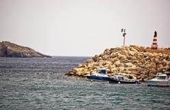Un mare del mare con una casa leggera sulla parete di pietra del porto fotografia stock
