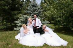 Un marié avec trois mariées Image stock