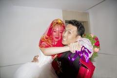 Un marié chinois tient sa jeune mariée avec des bras images libres de droits