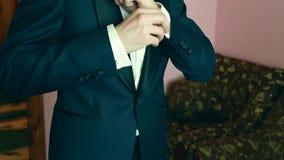 Un marié mettant sur des boutons de manchette comme il obtient habillé dans le tenue de soirée Le procès du marié clips vidéos