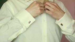 Un marié mettant sur des boutons de manchette comme il obtient habillé dans le tenue de soirée Le procès du marié banque de vidéos