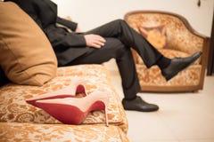 Un marié s'assied sur le sofa à l'arrière-plan pour une paire de rose salut Photographie stock