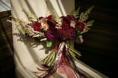 Un mariage a ébouriffé le bouquet avec des dahlias de Bourgogne et les roses crème avec des rubans se tient sur une chaise, allum image stock
