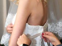 Un mariage, une jeune mariée dans une belle robe de mariage blanche et son amie l'aide à s'habiller, une garde-robe de mariage Images stock