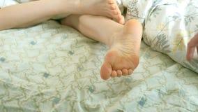 Un marido cariñoso despierta a su esposa, cosquillas divertidas sus pies almacen de video