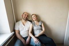 Un marido y una esposa de la pareja de matrimonios se est?n sentando en la esquina de la cocina fotos de archivo libres de regalías