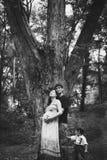 Un marito, una moglie incinta e un piccolo figlio stanno stando vicino ad un grande albero, il bambino sta tenendo un papà dai su fotografia stock