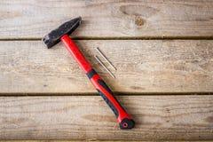 Un marteau avec une poignée rouge et deux clous images libres de droits