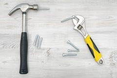 Un martello d'argento, una chiave, parecchi bulloni di vite e perni su fondo di legno leggero Fotografie Stock Libere da Diritti