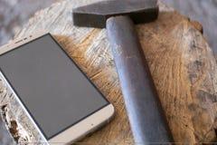 Un martello si trova accanto ad un telefono cellulare immagini stock