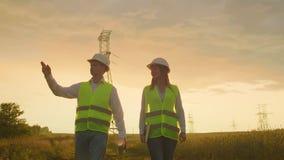 Un maschio dell'elettricista e femminile nei campi vicino all'elettrodotto È un elettricista che dirige stock footage