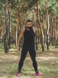 Un maschio muscolare che fa gli esercizi per le sue mani su uno sfondo naturale Fotografia Stock