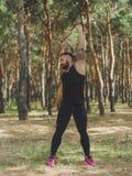 Un maschio muscolare che fa gli esercizi per le sue mani su uno sfondo naturale Immagine Stock