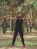 Un maschio muscolare che fa gli esercizi per le sue mani su uno sfondo naturale Fotografia Stock Libera da Diritti